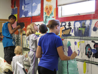 What fun! Children paint a mural inside one of the buildings at St. Lucy's Roman Catholic Church