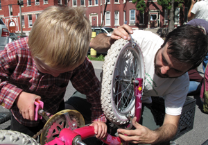 Nicholas Turner, 4, gets help fixing his sister's bike from volunteer Frank Cetera at the St. Lucy's Roman Catholic Church hub.
